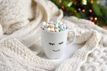 Warm, Cozy  Holiday Season Composition, Cup With Smiley Face, Cacao And Mini Marshmallows, Christmas Tree With Lights On Background.