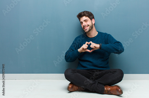 young handsome man sitting on floor looking bewildered and astonished, with hand Canvas Print
