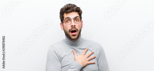 Fotomural  young manager man feeling shocked, astonished and surprised, with hand on chest