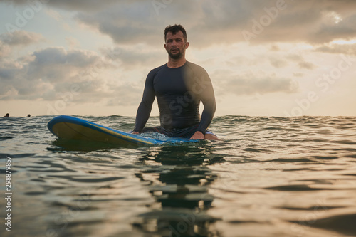 Male surfer getting ready for ride on the ocean wave against beautifull sinset l Wallpaper Mural
