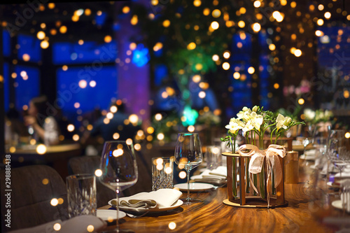 Fotomural  Blurred party background with served table with bouquet of flowers and people sitting at restaurant, bar or night club with colorful lights bokeh