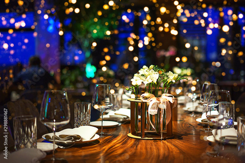 Papiers peints Restaurant Blurred party background with served table with bouquet of flowers and people sitting at restaurant, bar or night club with colorful lights bokeh.