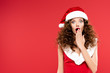 canvas print picture - happy surprised girl gesturing in santa costume, isolated on red