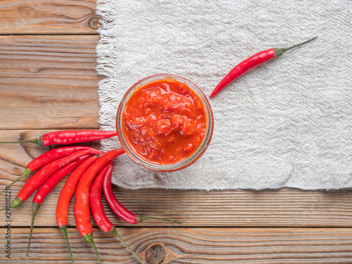 La pose en embrasure Hot chili Peppers Top Close up view of a glass jar of harissa with hot chili pepper on a white linen towel. With copy space.