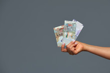 Beautiful Female Hands Hold Kuwaiti Dinars On A Gray Background. Copy Space, Gray Background