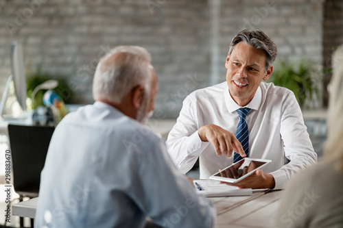 Happy insurance agent using digital tablet while talking with mature clients in the office.