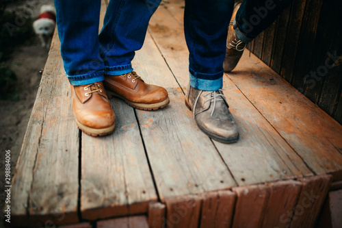 Fototapeta Cropped photo young legs in stylish shoes, married couple, husband and wife on a wooden bridge near lake. Rear view of couple standing on pier. obraz na płótnie