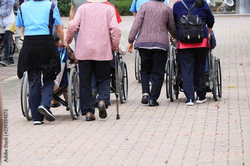 Photo 高齢者と介護士の散歩風景