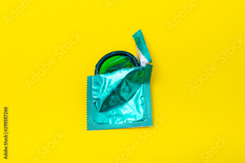 Fotografía Condom half out of package on a yellow background