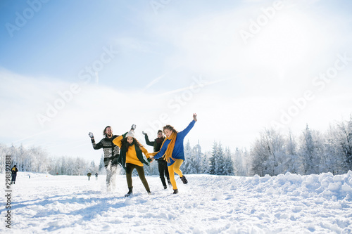 Group of young friends on a walk outdoors in snow in winter forest, having fun.
