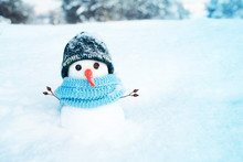 Portrait Of A Little Snowman In A Shapke And Scarf On Snow On A Sunny Winter Day.  Christmas Card