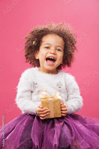 Fotografiet Happy little girl holding a shiny gift box