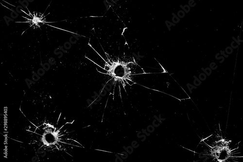 Fotomural holes in the glass with cracks isolated on a black