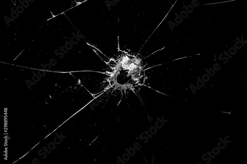 Fotografía  hole in the glass with cracks isolated on a black background