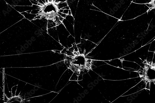 Photo holes in the glass with cracks isolated on a black