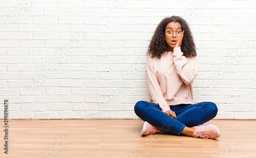 young african american black woman feeling shocked and astonished holding face t Wallpaper Mural