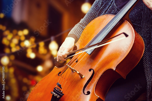 A young girl plays the cello in the dark. Hands on cello christmas - 298897095