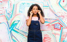 Young Pretty African American Woman Looking Angry, Stressed And Annoyed, Covering Both Ears To A Deafening Noise, Sound Or Loud Music Against Graffiti Wall