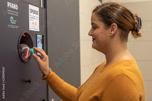 Valokuva  Junge Frau wirft Pfandflaschen in Automaten