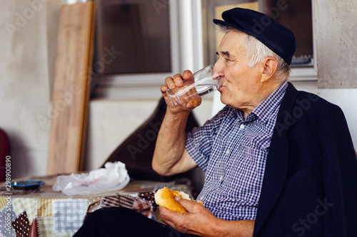 Fotomural  Senior old man pensioner drinking water while eating fast food burger sitting by