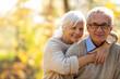 Leinwandbild Motiv Elderly couple embracing in autumn park