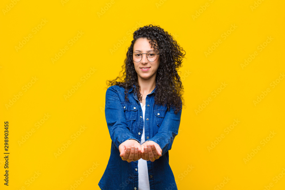 Fototapety, obrazy: young pretty woman smiling happily with friendly, confident, positive look, offering and showing an object or concept against orange wall