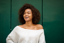 Laughing Young African American Woman Against Green Background