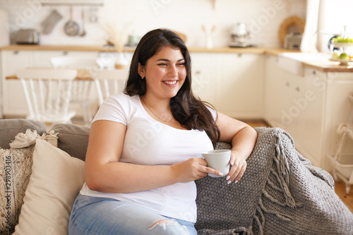 Portrait of cheerful charismatic young overweight female with big breast and lon Fototapete