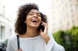 Close up happy young african american woman with curly hair talking with mobile phone outside