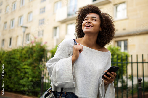 Obraz Portrait of smiling young african american woman walking in city with cellphone in hand - fototapety do salonu
