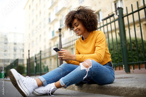 cool young african american woman sitting outside on street with cellphone