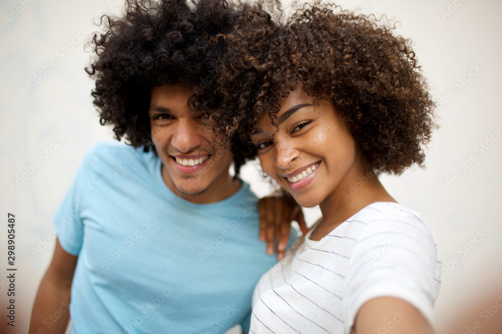 Fototapety, obrazy: Close up happy african american couple taking selfie by white background