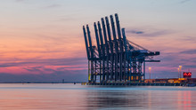 Row Of Container Terminal Cranes At Red Colored Sunset In Port Of Antwerp, Belgium