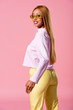 stylish, blonde african american woman smiling at camera isolated on pink, fashion doll concept
