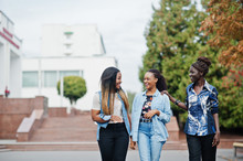 Group Of Young Black Female Friends Hanging Out In The City. Multiracial African Women Walking By The Street And Discuss.