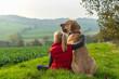 Beste Freunde - ein Mädchen sitzt in der Natur und umarmt seinen besten Freund, einen Broholmer, und beide genießen den Sonnenuntergang