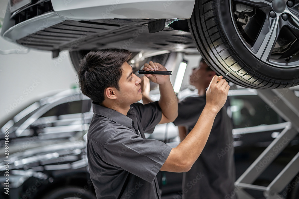Fototapeta Asian mechanic Checking and torch tire in maintainance service center which is a part of showroom, technician or engineer professional work for customer, car repair concept