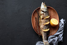 Baked Fish With Lemon And Herbs. Dorado On A Plate With Vegetables. Tasty Fried Dorado Fish Or Bream With A Gilt Head With Lemon Slices And Herbs On A Plate, Top View, Close-up. Place For Recipe