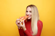 Happy woman eating tasty pizza for lunch in the pink studio