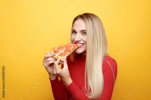 Fototapeta Happy woman eating tasty pizza for lunch in the pink studio obraz