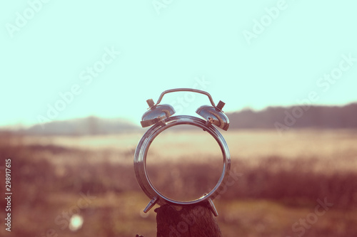 Photo Stands Cappuccino Old alarm clock on the background of the sun, fields and mountains in retro style.