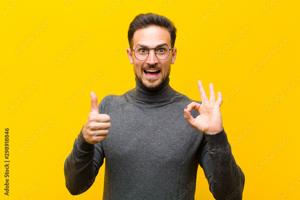 Fototapety, obrazy: young handsome man feeling happy, amazed, satisfied and surprised, showing okay and thumbs up gestures, smiling against orange wall