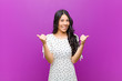 canvas print picture - young pretty latin woman smiling joyfully and looking happy, feeling carefree and positive with both thumbs up against purple wall
