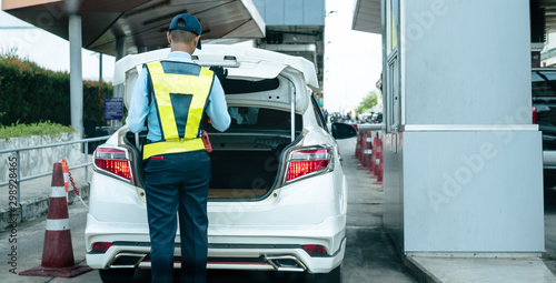 Fototapeta Back view of Thai security guard checking car truck at the entrance to the parking lot at shopping mall