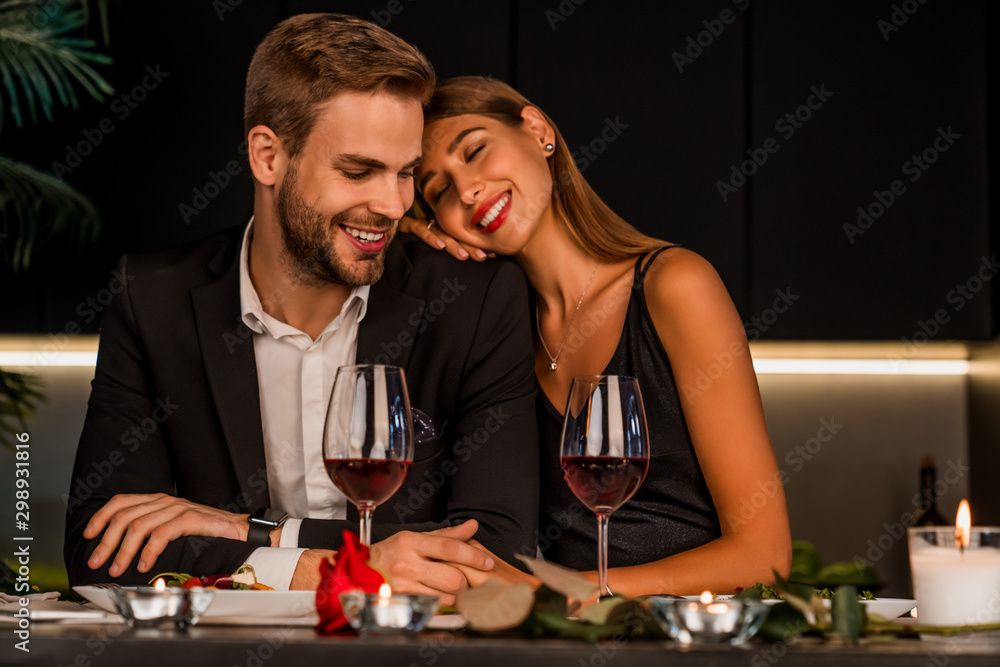 Fototapeta Excited loving couple celebrating special event with wine and candles , having dinner together