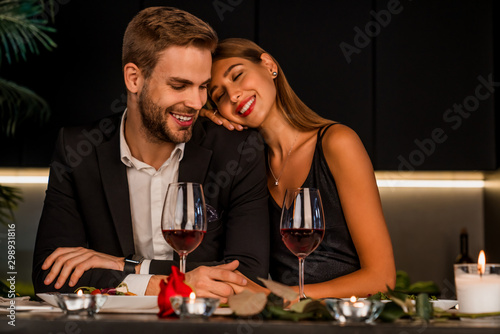 Fototapeta Excited loving couple celebrating special event with wine and candles , having dinner together obraz