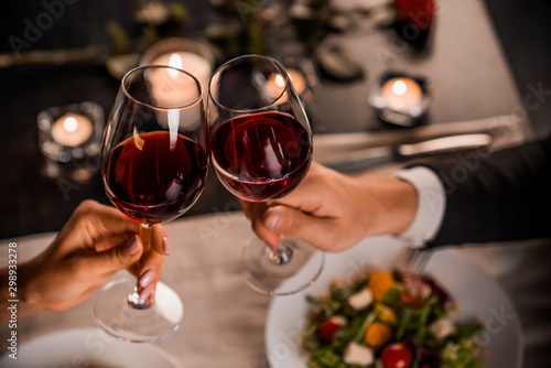 Obraz Close up of young couple toasting with glasses of red wine at restaurant - fototapety do salonu