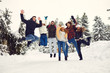 canvas print picture - Friends jumping in the snow in the park in winter