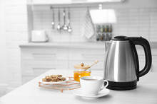 Modern Electric Kettle, Cup Of Tea And Cookies On Wooden Table In Kitchen