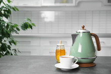 Modern Electric Kettle, Cup Of Tea And Honey On Grey Table In Kitchen